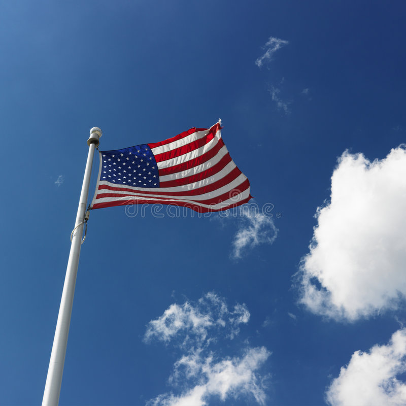 American flag. Low angle view of American flag flying with cumulus cloud formation in blue sky royalty free stock image