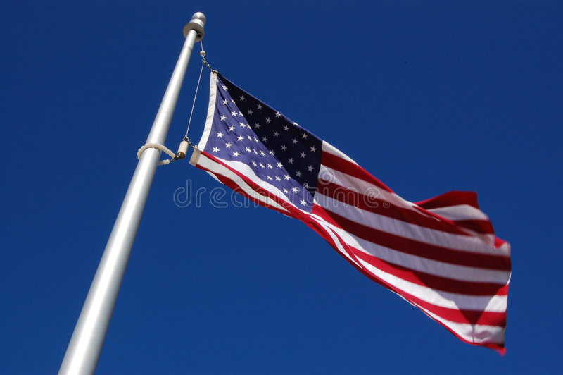 American Flag. Flying in the wind against clear blue sky stock image