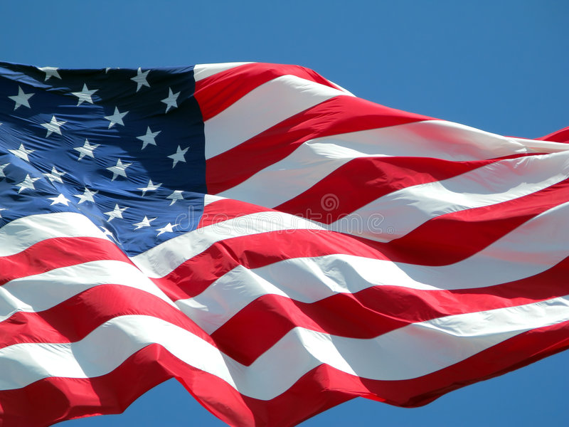 American Flag. Waving American flag against a blue sky background stock images
