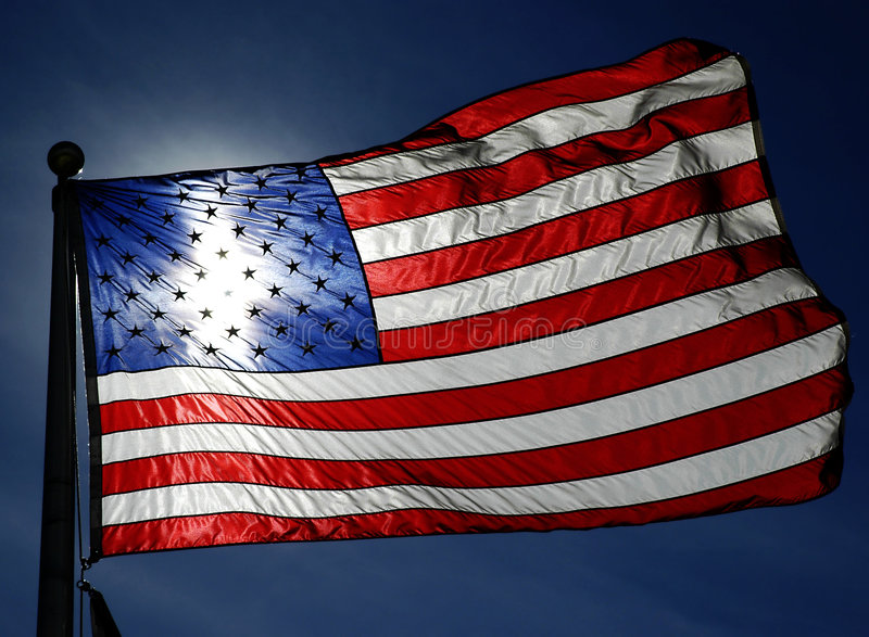 American Flag. Detail closeup of American Flag blowing in breeze with blue sky stock photo