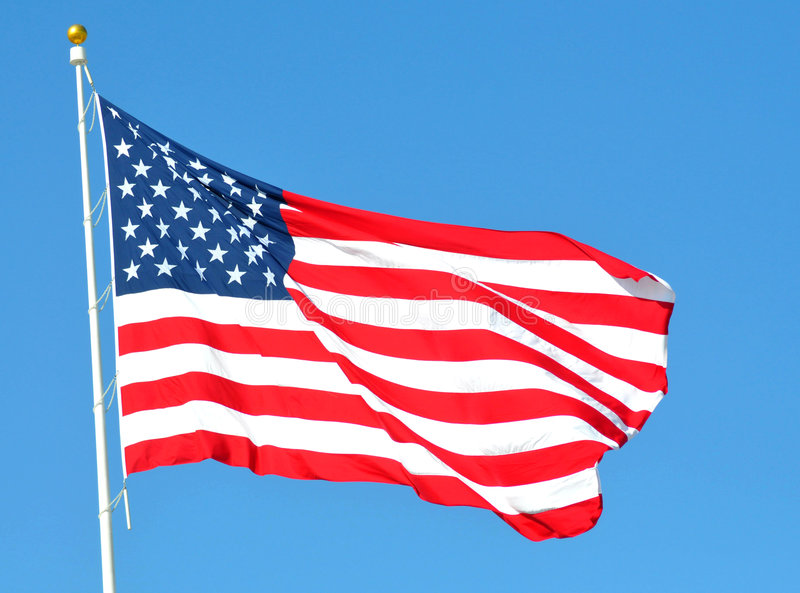 American flag. The American flag in the wind against the blue sky stock images