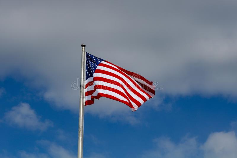 An American Flag. Against a blue sky with clouds royalty free stock photo