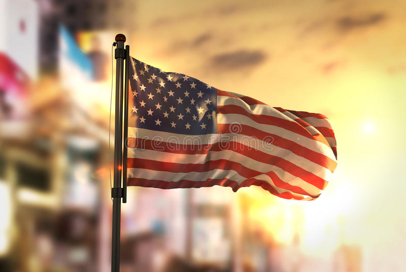 American Flag Against City Blurred Background At Sunrise Backlight. Sky stock photography