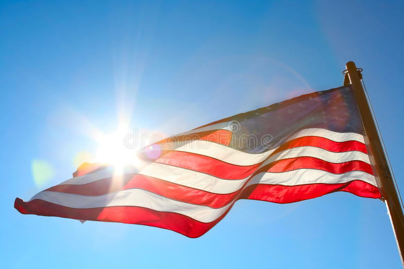 American flag against the sun. American flag backlit from the sun royalty free stock photos