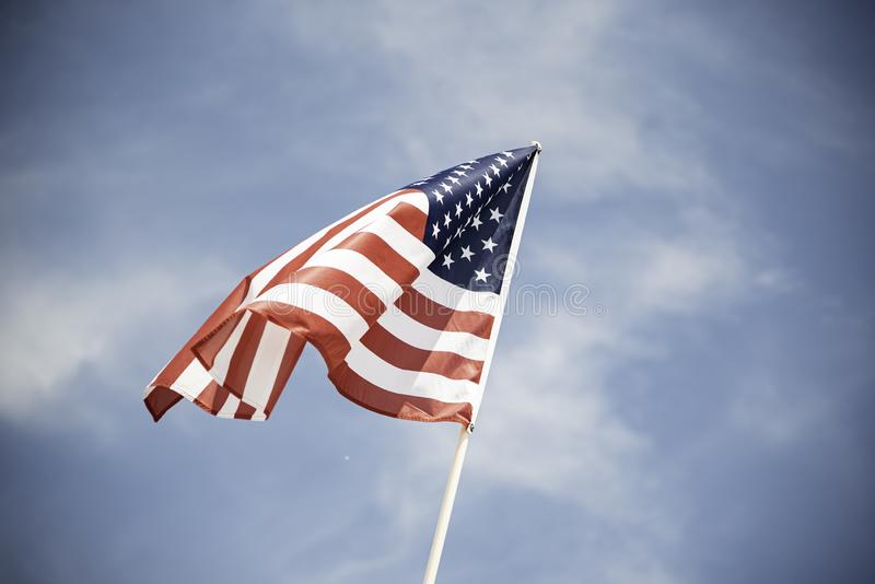 American Flag. An American flag fluttering in the wind against a blue sky with clouds stock photo