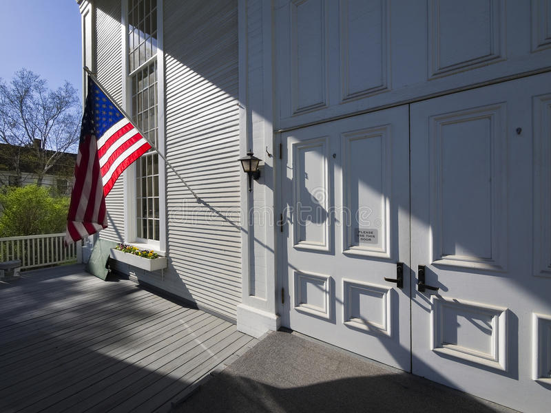 American flag back lit on front of New England church royalty free stock images