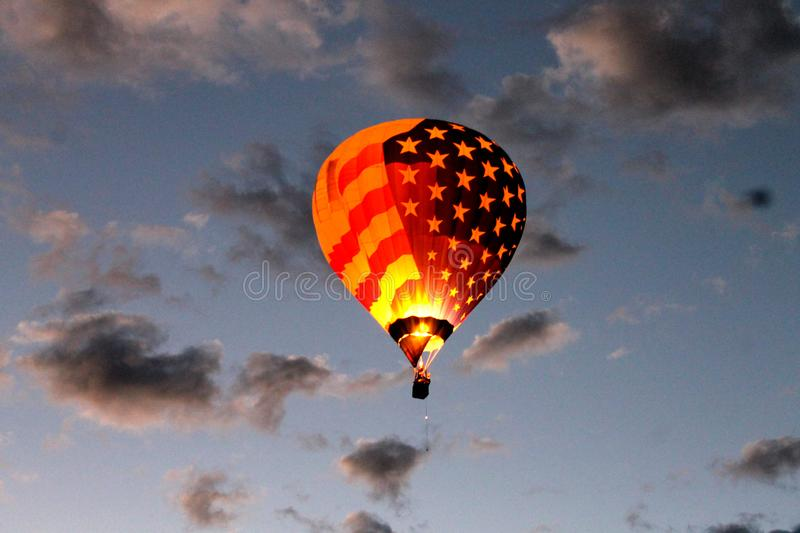 American Flag balloon Dawn Patrol flying the skies at the Albuquerque International Balloon Fiesta. American Flag balloon flying over Albuquerque on a chilly stock photography