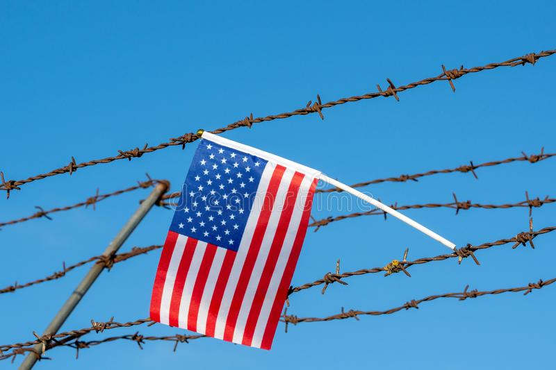 American flag on barbed wire fence. Borders protection,social issues on refugees or illegal immigrants stock photography