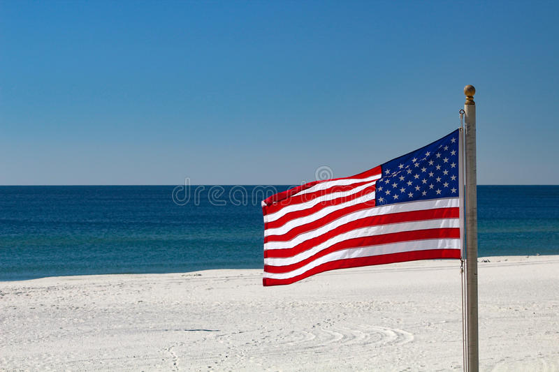 American Flag on the Beach. American flag flying on a white sand beach royalty free stock photos