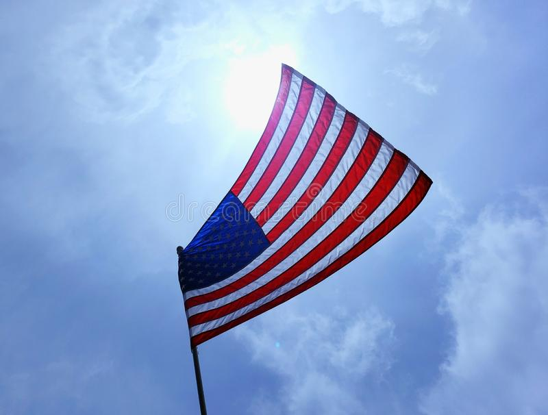 American Flag Blowing In The Breeze. American flag at interesting angle blowing in the breeze against sun sky and clouds patriot patriotic usa starsandstripes stock photo