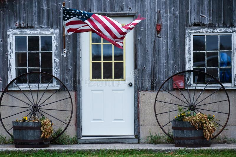 American Flag blowing in the wind by a door and two wagon wheels stock photography