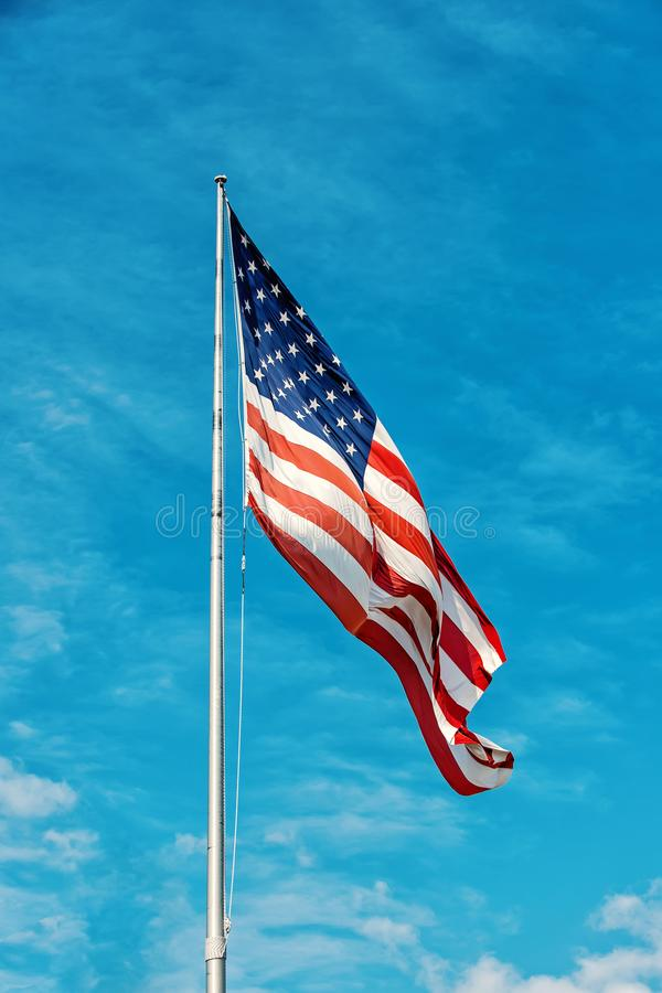 American flag on the blue sky. American flag against blue sky at summer day stock photography