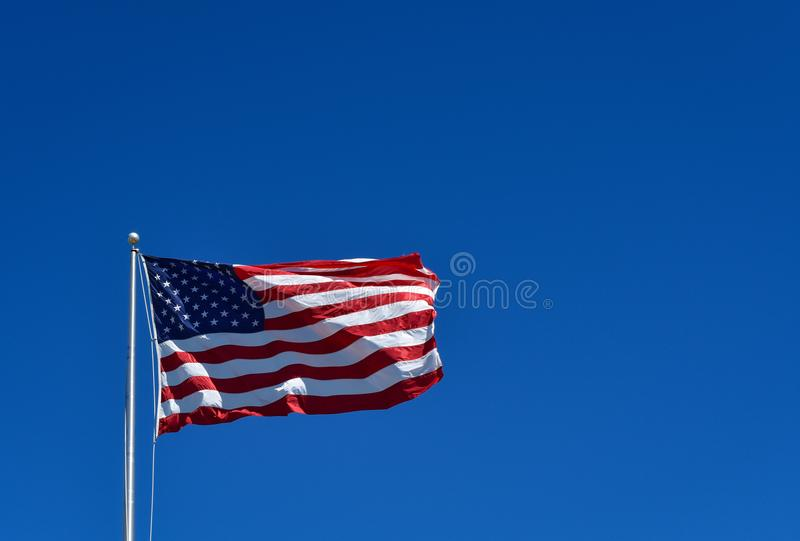 American Flag on Blue Sky. Stunning American Flag flapping in the wind with clear blue skies stock photography