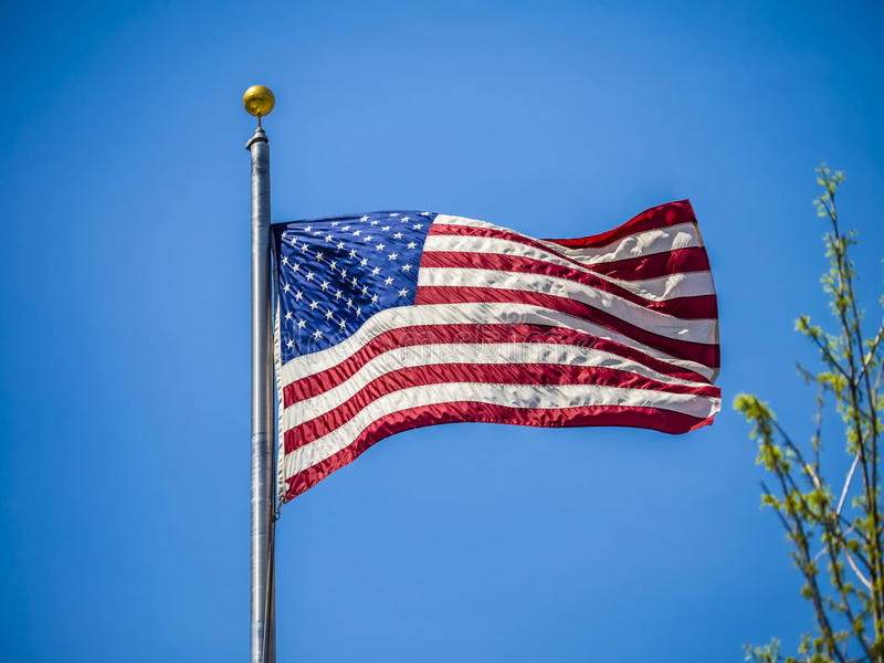 American flag on the blue sky. On a sunny day stock images