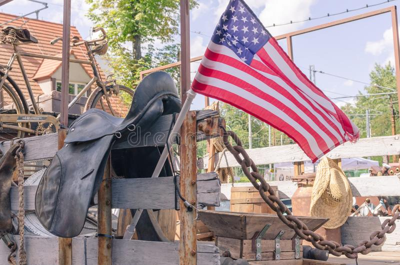 American flag on the bodywork of vintage Ford truck with old farm stuff- straw hat,  rusty bike, rusty cans and the saddle royalty free stock photo