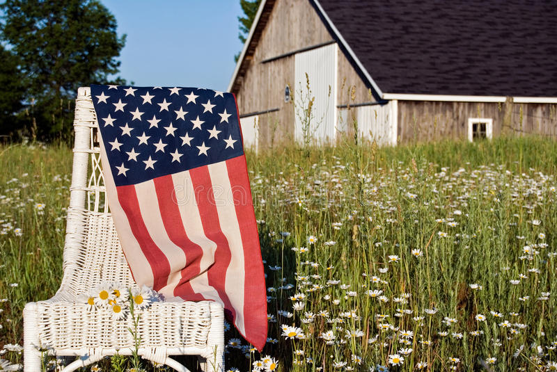 American flag on chair. American flag draped over wicker chair in daisy field royalty free stock photos