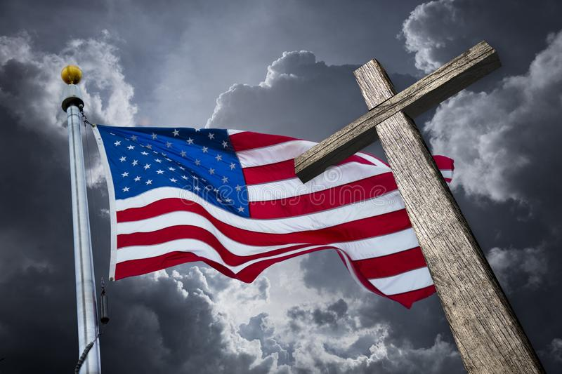 American flag with a christian cross. And dramatic clouds royalty free stock image