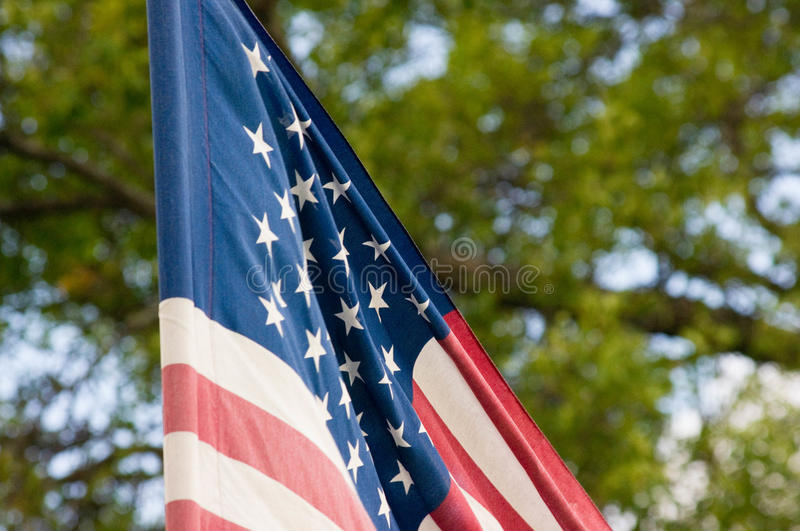 American flag close up. Close up of the American flag with bokeh trees in background royalty free stock photography