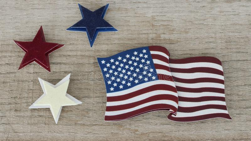 American flag laying flat on a reclaimed wood background. American flag close up next to a red white and blue star on a natural wood background stock image
