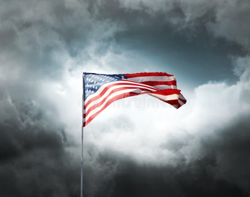 American flag on a cloudy dramatic sky. American flag on a dark cloudy dramatic sky stock photos