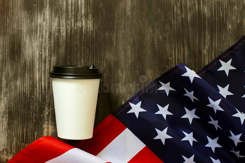 American flag and coffee paper cup on a old wooden background stock image