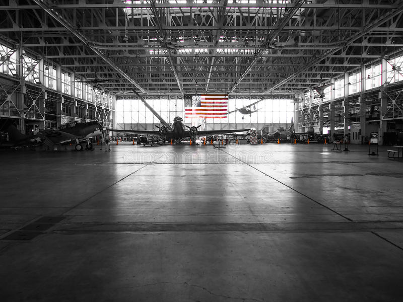 American Flag Color in Black and White Background Airplane Hangar. The American flag stands out in the background of this black and white photo of an airplane stock photo