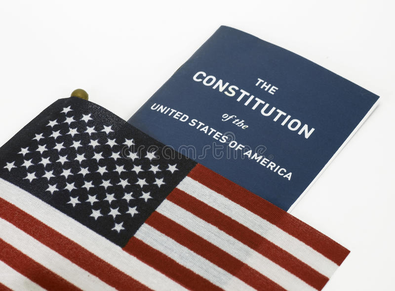 American Flag and Constitution. Red, white, and blue American flag partially covering a copy of the Constitution of the United States against a white background royalty free stock photography