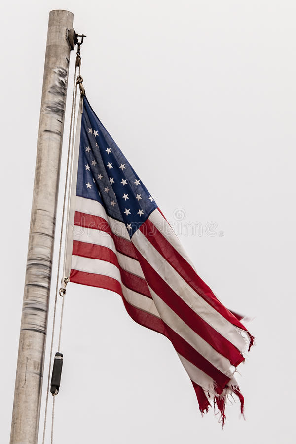 American Flag in disgraceful-condition,tattered,torn,. An American Flag in disgraceful-condition,tattered,torn,which should be replaced royalty free stock image