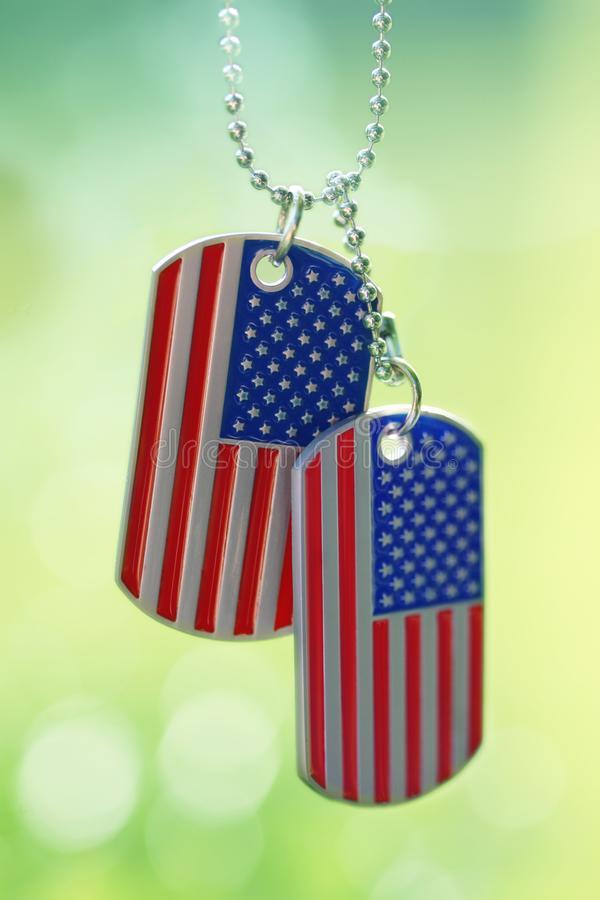 American flag dog tags hanging outside. Red, white, and blue American flag dog tags hanging outside royalty free stock image
