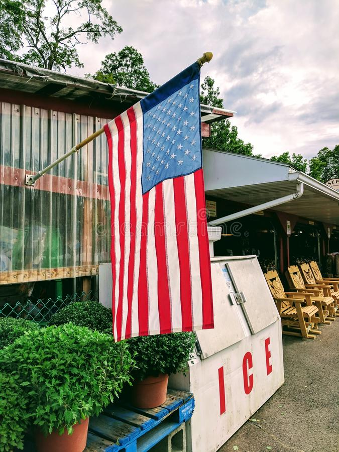 American flag next to ice freezer. American flag at farm market storefront. Rustic Americana royalty free stock photography