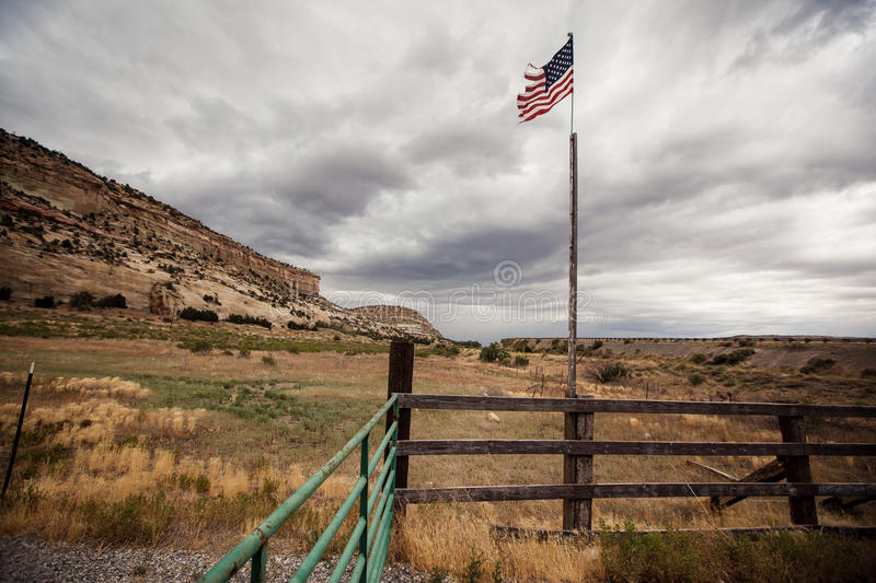 American flag on the field. With dramatic gray sky stock image