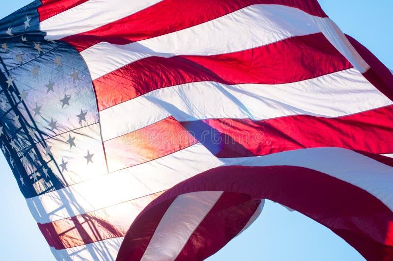 An American flag on a fire truck ladder. A giant American flag is flown from the ladder of a fire truck in Barnstable, Massachusetts, USA stock photos