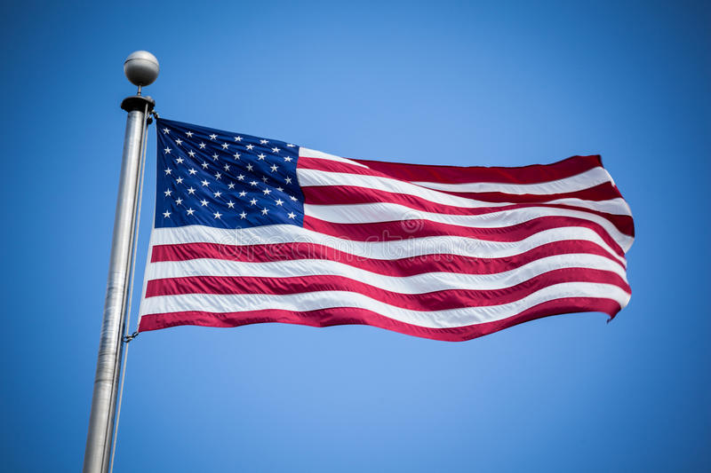 American Flag. On a flagpole blowing in the wind against a blue sky stock photos
