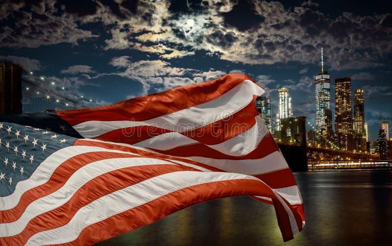 American flag flying the against a dusk sky New York, Brooklyn Bridge and Manhattan stock photos