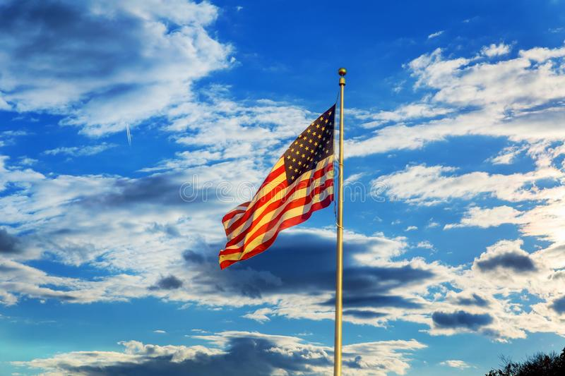 American flag flying in the breeze against blue sky with white clouds royalty free stock image