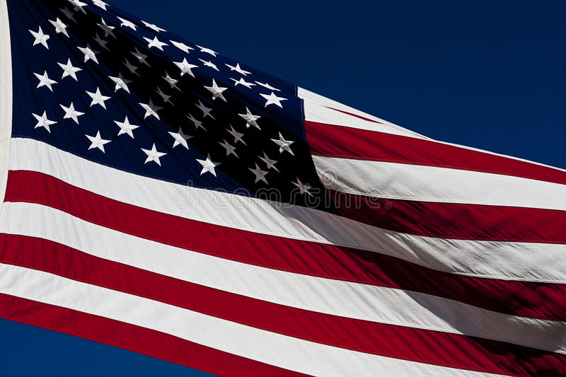 American Flag. Flying in the breeze against a clear blue sky royalty free stock photos