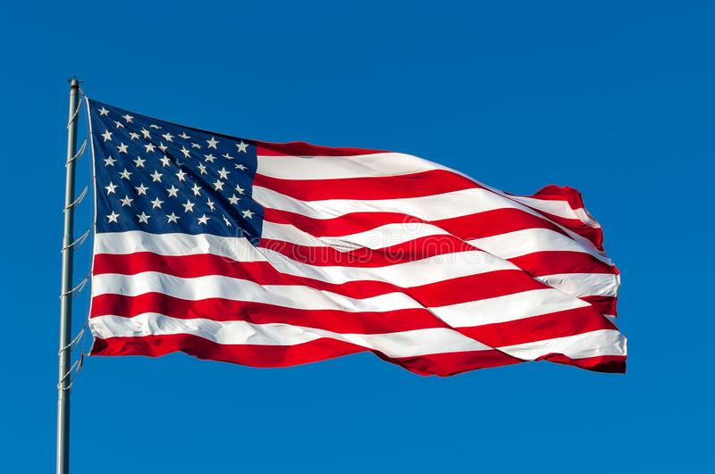 American flag against a blue sky. An American flag flying in the breeze against a cloudless bright blue sky stock images