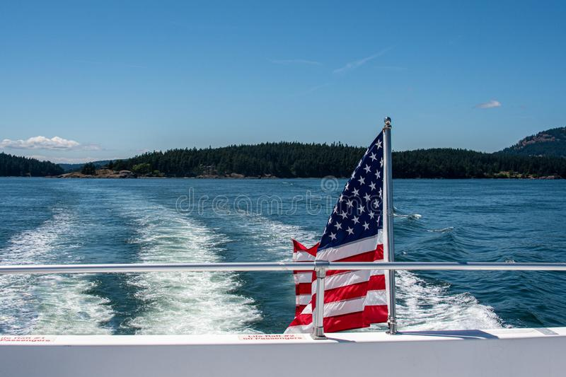 American flag flying off the back of a boat on the Salish Sea in the San Juan Islands on sunny blue sky day royalty free stock image