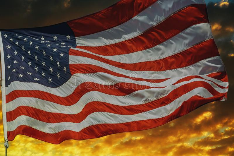 American flag flying, over beautiful Sunset sunrise with clouds,. American flag flying, flag USA over beautiful Sunset sunrise with clouds, in sky sunrise clouds stock image