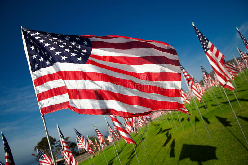 American Flag Flying in Wind. An American flag flies in the wind against a background of hundreds of other flags stock photo