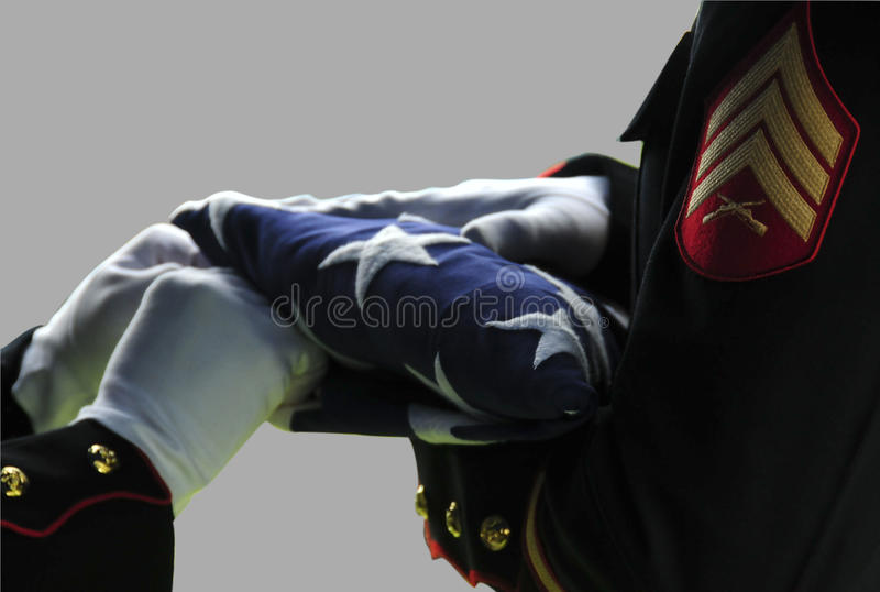 American flag folding ceremony. Details of uniformed servicemen folding American flag in traditional ceremony, light background royalty free stock photography