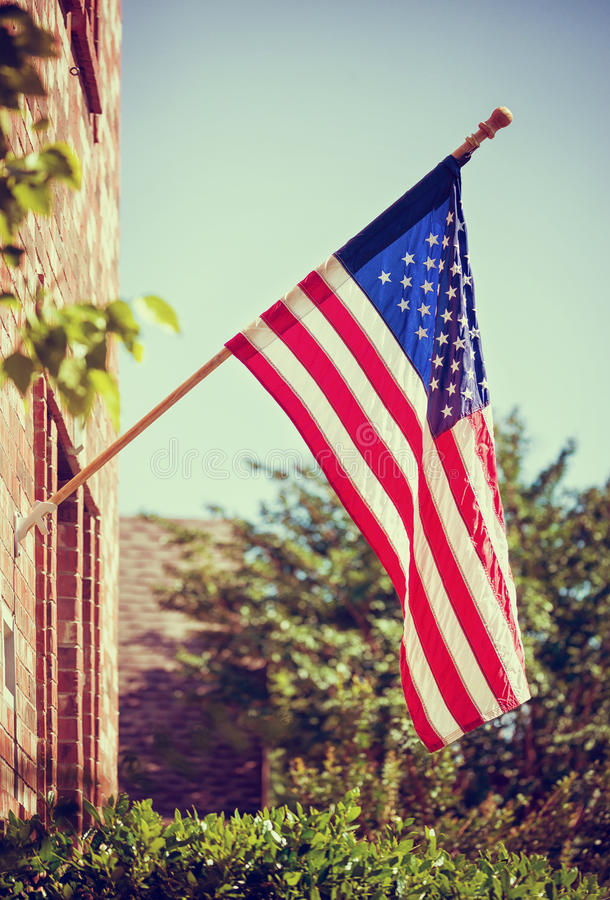 American flag in front of a home. Patriotic American flag hanging in front of a home. Blue sky with copy space. Vintage filter effects royalty free stock photos