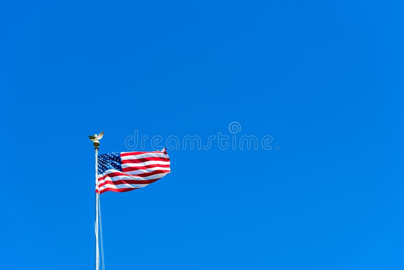 American flag at the Golden Gate National Cemetery, San Bruno, California, USA. Isolated on blue background.  royalty free stock photo