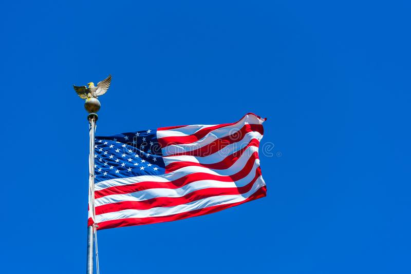 American flag at the Golden Gate National Cemetery, San Bruno, California, USA. Isolated on blue background.  royalty free stock photography