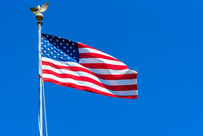 American flag at the Golden Gate National Cemetery, San Bruno, California, USA. Isolated on blue background.  stock photography