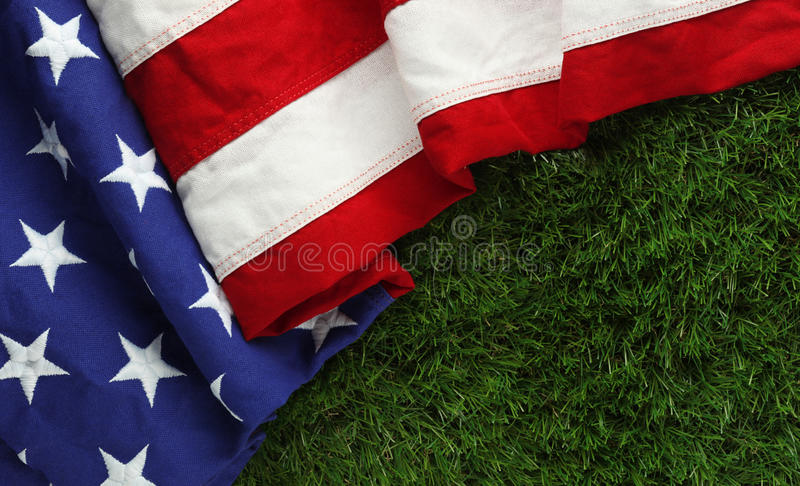 American flag on grass for Memorial Day or. Red, white, and blue American flag on grass for Memorial Day or Veteran`s day background stock photo