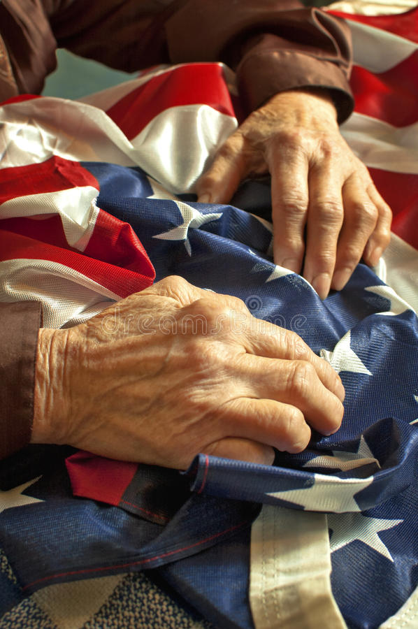 Hands on American flag. Old womans hands holding an American flag royalty free stock photos