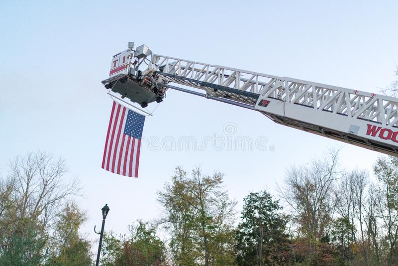 American flag hanging from fire truck ladder. An American flag hanging from a fire truck ladder during the day. Patriotic symbol with first responder vehicle royalty free stock photography
