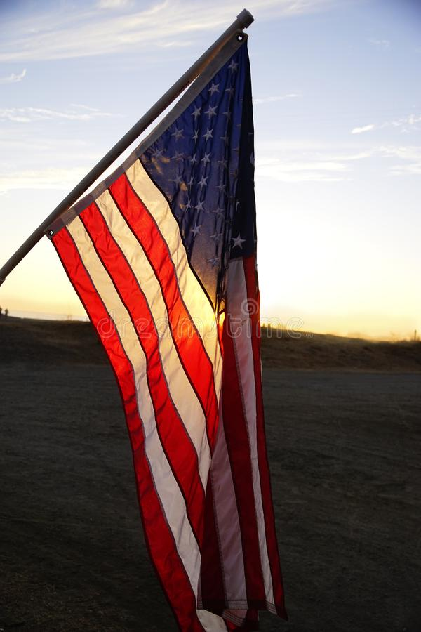American Flag. Hanging at sunset. Sun illuminating the flag from behind. Light blue sky above, dark foreground. Vertical stock image