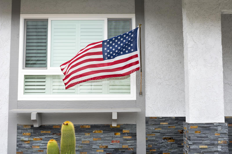 American flag on house. American flag blowing in the breeze while hanging on a residential home symbolizes a patriotic holiday in the United States stock image